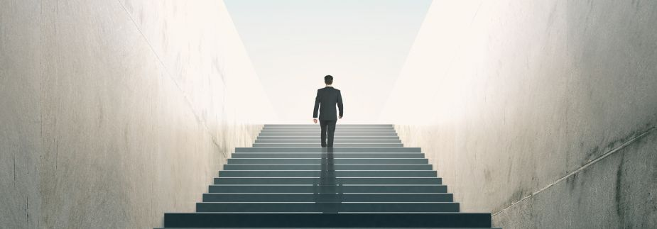 Picture of a business man climbing the stairs to success