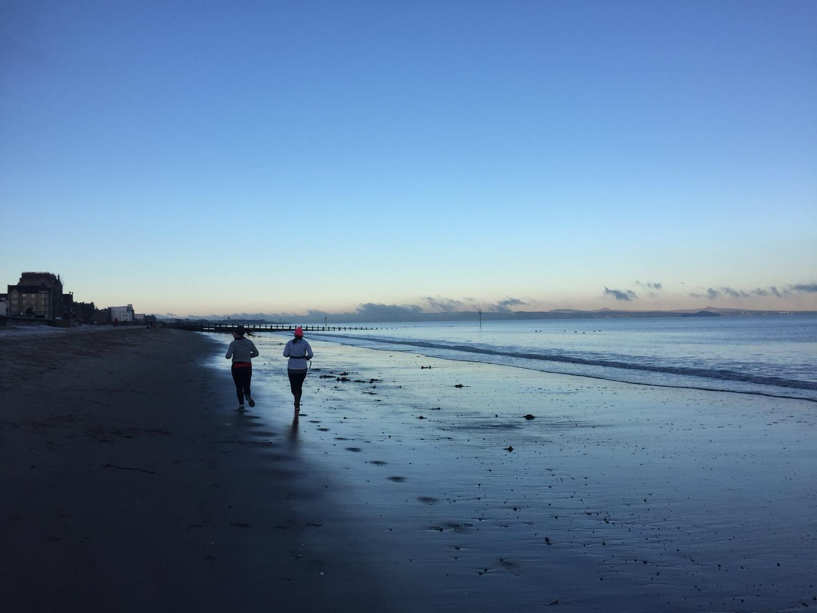 two people running on a beach