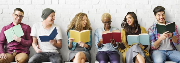 Happy professionals reading top books for entrepreneurs