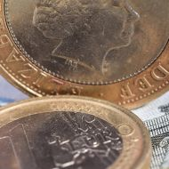Picture of a euro coin and pound coin on notes