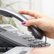 Woman picking up telephone